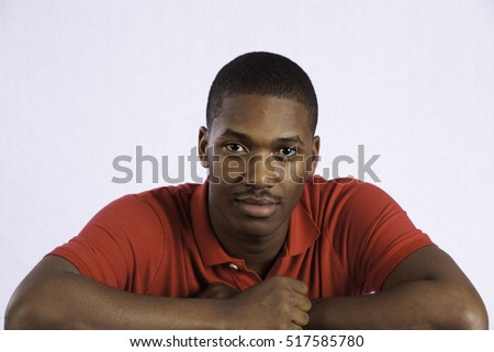 Handsome Black man in red shirt, looking thoughtful and pensive