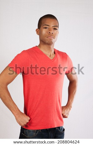 Handsome Black man in red shirt, with hands on his hips and looking thoughtful and serious - stock photo