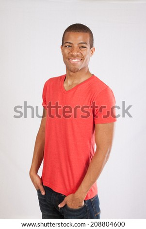 Handsome Black man in red shirt with his hands in his pockets and, with a happy smile