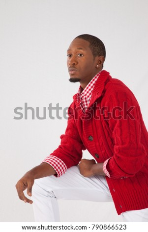 handsome black man in red sweater, looking thoughtful