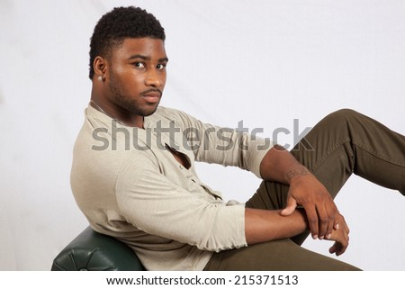 Handsome Black man in shirt and slacks, sitting, leaning back on a bench and looking thoughtful,
