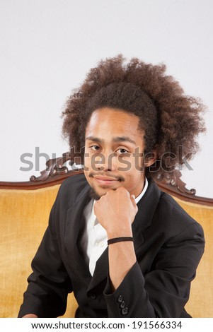 Handsome black man in suit, sitting on a gold couch and looking at the camera with his hand on his chin in a thoughtful position - stock photo