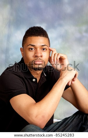 Handsome black man sitting and thinking with a serious expression