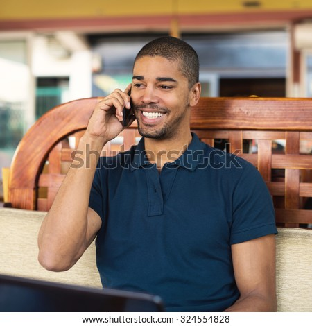 Handsome black man sitting at cafe bar and talking on mobile phone. He is looking aside and smiling. - stock photo