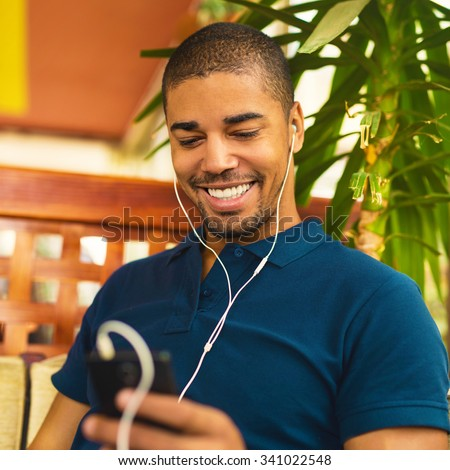 Handsome black man sitting at cafe bar, holding mobile phone and smiling. He is listening music and looking at smart phone.