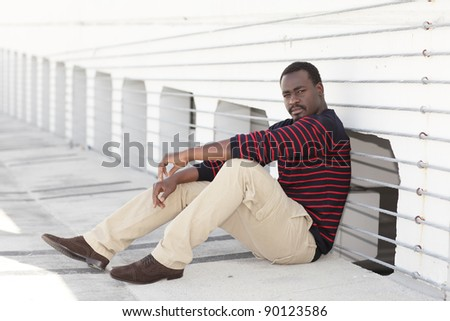 Handsome black man sitting in an empty parking lot - stock photo