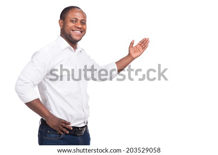 handsome black man standing and smiling. Man raised left hand palm - stock photo