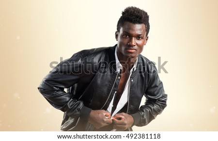 Handsome black man with leather jacket over ocher background