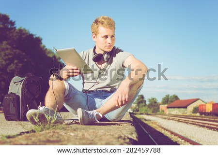 Handsome blond Caucasian young man with tablet, headphones and backpack sitting by the train rails looking away. Horizontal, retouched, filter applied. - stock photo