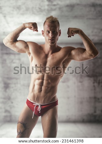 Handsome blond muscular shirtless young man doing biceps pose in empty concrete room - stock photo
