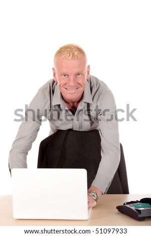 Handsome blond smiling mid forties businessman at desk with laptop.  Studio white background