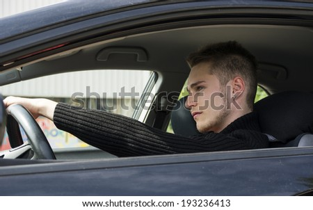 Handsome blond young man sitting in his car, looking in front of him