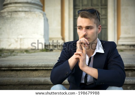 Handsome blond young man with marble columns behind him, sitting on stair steps, thinking - stock photo