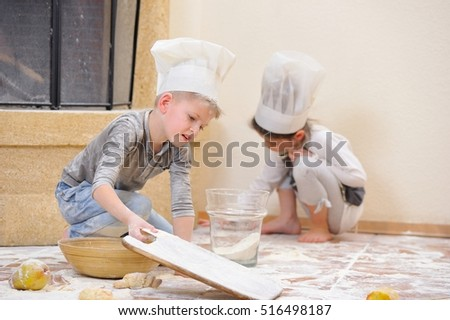 Handsome blue eyed kids in chef's hats near the fireplace: a boy sitting and playing cook with his pretty cousin, they are totally stained with flour and having fun