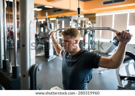 Handsome bodybuilder doing heavy weight exercise - stock photo