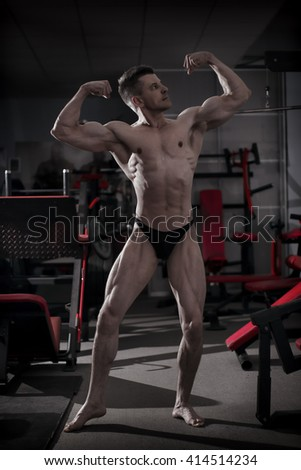 Handsome bodybuilder posing in gym. Perfect muscular male body. Toning image - stock photo