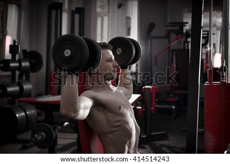 Handsome bodybuilder with muscular torso workout with dumbbells on athletic bench in gym. Perfect muscular male body. Toning image