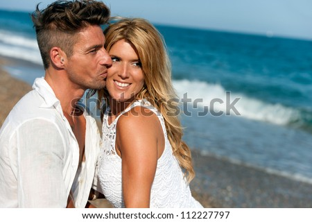 Handsome boy kissing his girlfriend on her cheek outdoors.