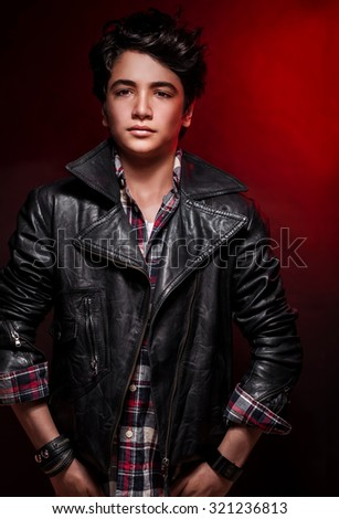 Handsome boy portrait over red background, wearing leather jacket and stylish shirt, fashionable autumn clothes, funky teens fashion