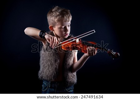 handsome boy proudly plays his fiddle - stock photo
