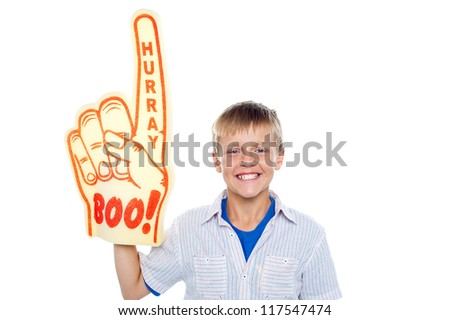 Handsome boy with a hurray boo foam hand pointing skywards on isolated white background - stock photo