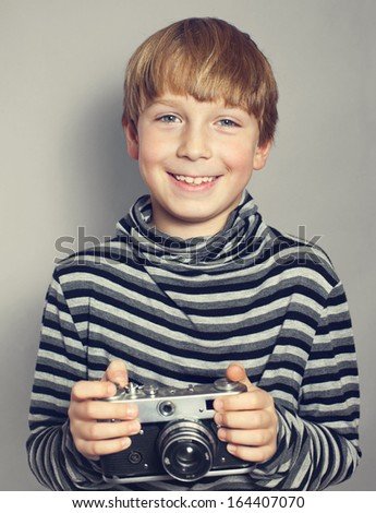 handsome boy with an old camera - stock photo