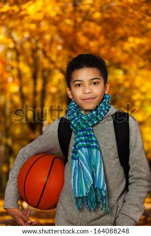 Handsome boy 10 years old standing in the autumn park under maple trees with orange basketball ball wearing casual clothes with scarf - stock photo