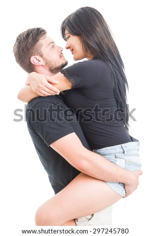 Handsome boyfriend holding happy and beautiful girlfriend on white background - stock photo