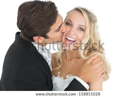 Handsome bridegroom kissing his wife on her cheek while embracing her - stock photo
