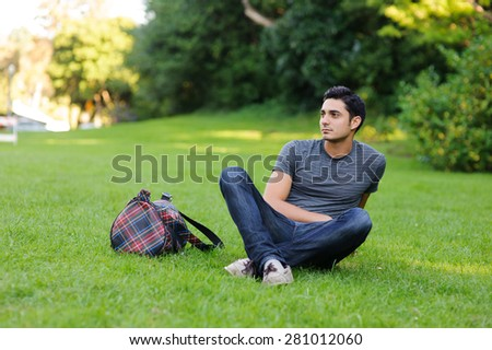 Handsome brunet young man in casual clothing sitting in the park - stock photo