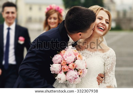Handsome brunette groom kissing beautiful bride in wedding dress with bouquet bridesmaids in background - stock photo