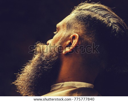 Handsome brunette hipster with stylish haircut and thick beard mustache on face on black backdrop , close up
