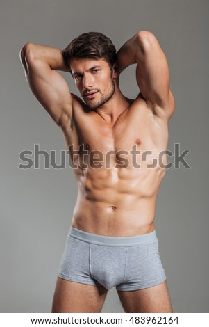 Handsome brutal athletic man posing isolated on a gray background