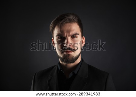 handsome brutal guy with beard on dark background in studio
