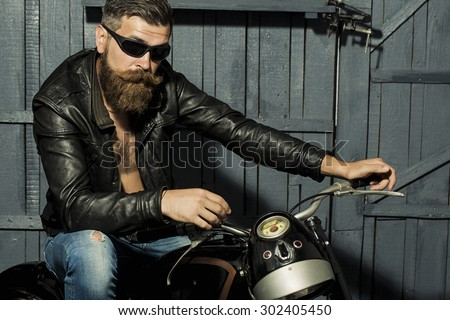 Handsome brutal unshaven male biker with long beard in brown leather jacket jeans and sun glasses sitting in garage on motorcycle looking forward on grey wooden background, horizontal picture - stock photo