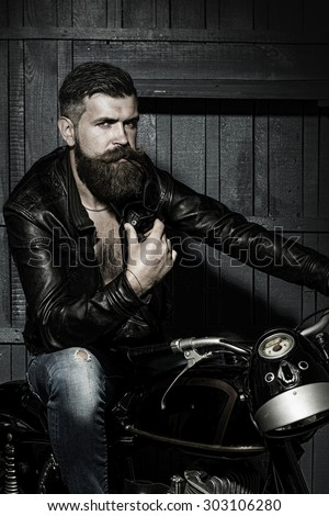 Handsome brutal unshaven sexual male biker in black leather jacket jeans with sun glasses sitting in garage on motor bike looking forward on wooden background, vertical picture - stock photo
