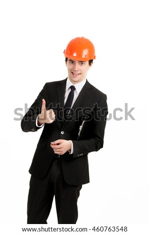Handsome builder is holding tape-measure in hands and showing sign with happiness. He is smiling and looking forward with joy. Isolated on background