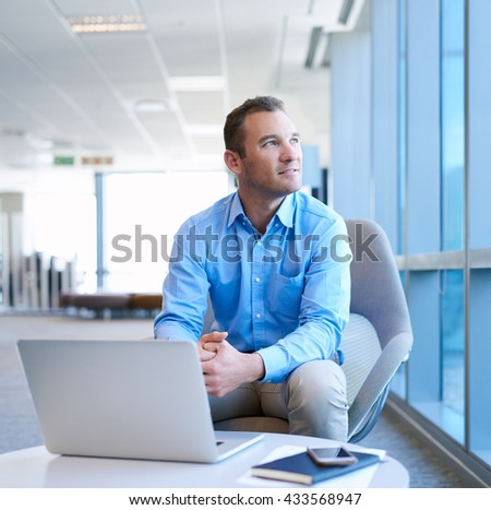 handsome business entrepreneur sitting in a bright modern office space with his laptop open bright modern office space