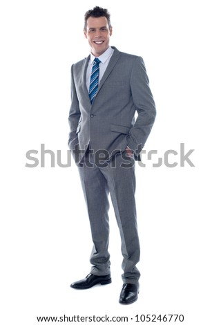 Handsome business executive posing with hands in pocket. Full length portrait - stock photo