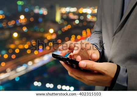 Handsome Business male in the city using his smartphone with Bokeh Background