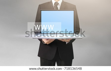 Handsome business man and suit holding laptop in hands