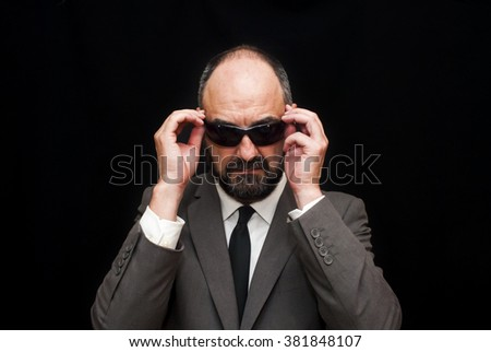 Handsome business man, bald and beard, over black background