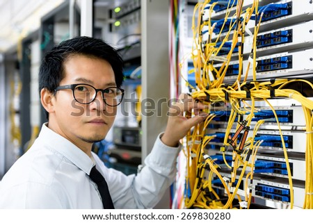 handsome business man engeneer in datacenter server room - stock photo
