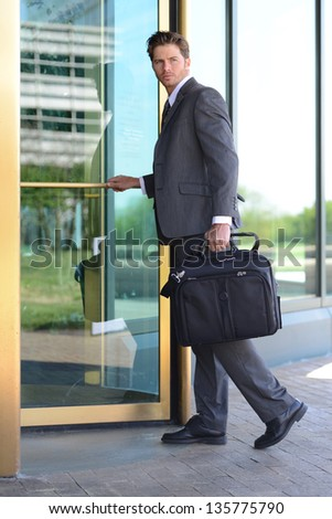 Handsome Business Man Entering Building through Revolving Doors - stock photo