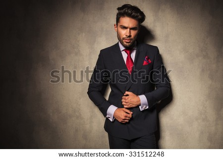Handsome business man fixing his jacket while looking at the camera. - stock photo