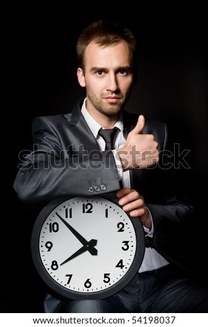 handsome business man holding clock, showing his thumb up - stock photo