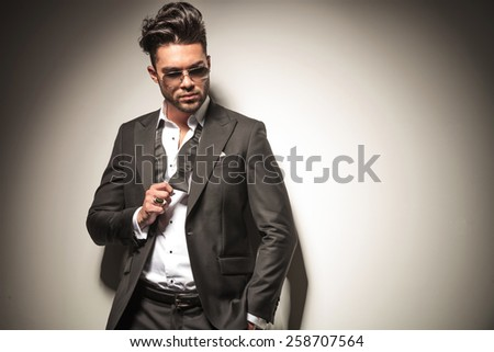Handsome business man holding his fist up, showing his ring while looking down. - stock photo