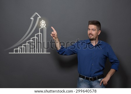 Handsome business man in casual clothes. Smiling man pointing out the diagram concerning profit business strategy on dark grey background. - stock photo