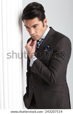 Handsome business man looking down while holding his hand to chis chin thinking. - stock photo