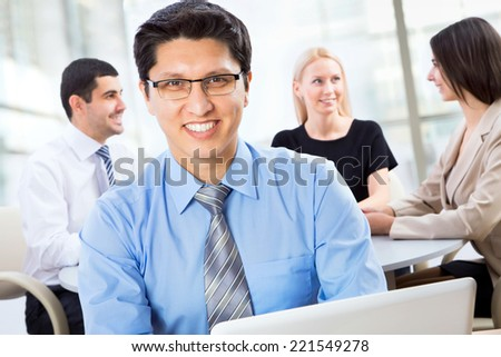 Handsome business man looking straight at the camera with his colleagues behind him - stock photo